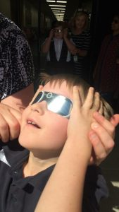student with eclipse glasses